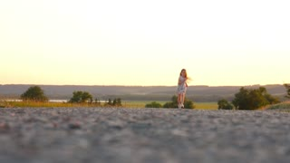 Little girl having fun run on the asphalt during the sunset in nature, lifestyle, outdoors.