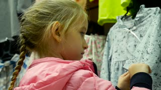 Little girl holding new dress in hands in children clothes boutique.