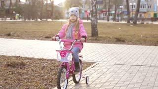Little girl in a trendy pink outfit with matching pink bike riding her bicycle along a lane in a wooded park, learning to ride a bicycle with training wheels. In the rays of sunset.