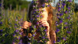 Little girl in flowers field. The child hides behind the flowers in the field.