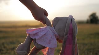 Little girl in pink festive dress holding big plush bunny toy at sunset. Silhouette of a child with a toy. Textile handmade toy bunny in on the girl hand. The concept of a child's dream.