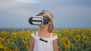 Little girl in virtual reality goggles in the sunflower field on sunset. Child looking at virtual reality glasses at sun.
