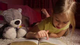 Little Girl is Reading a Book With Flashlights at Night. Happy Girl Plays at Home. Funny lovely kid having fun in children room.