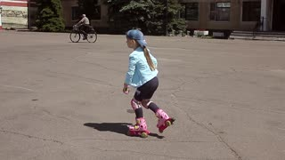 Little girl learning to roller skate in sunny summer park. Child wearing protection elbow and knee pads, wrist guards for safe roller skating ride. Active outdoor sport for kids.