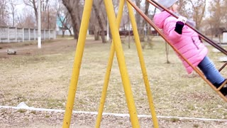 Little girl on swing in city park, happy child on swing. Concept girl in pink on a swing quickly. Child, Playing, Playground.