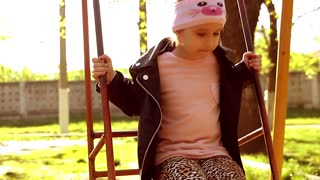 Little girl on swing in city park, happy child on swing. Concept girl in pink on a swing quickly.