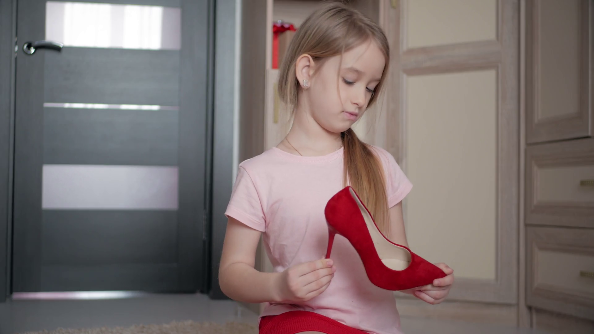 Little girl on the floor at home trying mom's red high heel shoes.