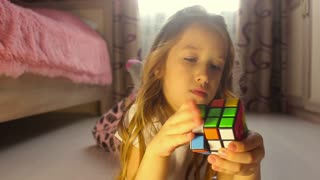 Little girl playing with rubik's cube .