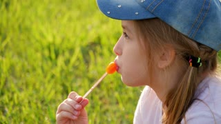 Little girl sit on grass and eats ice cream.