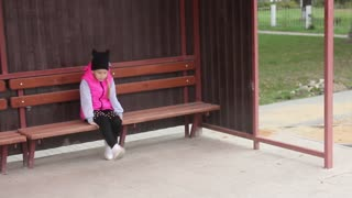 Little girl sitting on a bench waiting for transport at the bus stop.