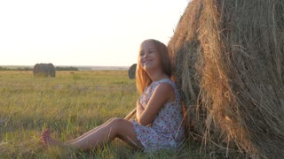 Little girl sitting on a coil of straw. Blonde pretty country girl sitting in a haystack.