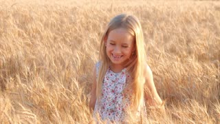 Little girl to wave hands on meadow with sunset.