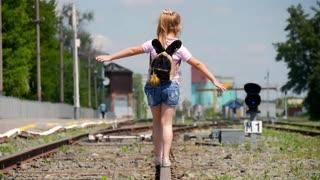 Little girl walking on the railway.