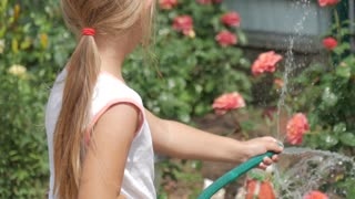 Little girl watering flowers in a garden.