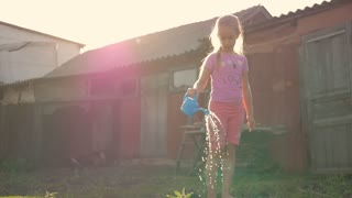 Little girl watering in the family garden at a summer day, sunset.