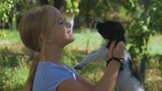 Little girl with a puppy in garden. A puppy in the hands of a girl.