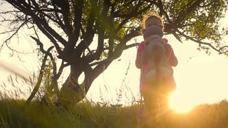 Little girl with teddy bear on nature.