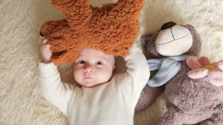 Little toddler is lying in bed with his teddy bear