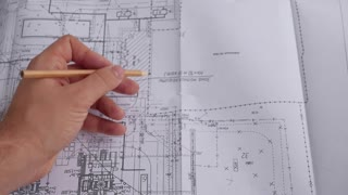 Macro close up of quantity surveyors hand reviewing technical drawing. Architect working on blueprint. Construction concept. Engineering tools. Top view.