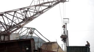 Magnetic crane loading scrap metals at junkyard.