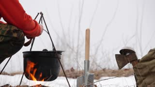 Man cooking food in a pot on the fire, cover pan with a lid, the tourist camping, outdoors, winter