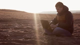 Man freelanser sitting on a sandy beach and working at a laptop, sunset or sunrise. Toned