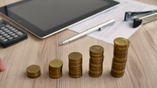 Man hand holding coin dollar on money coin stack arranged as a graph on wooden table. Hand of male or female finger step coins stack growing growth saving money. Business idea.