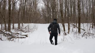 Man hiking in white winter forest with backpack. Recreation and healthy lifestyle outdoors in snowy nature. Travel Lifestyle concept adventure active vacations outdoor cold weather into the wild.
