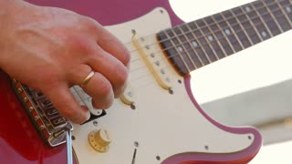 Man playing electric guitar with nature light.