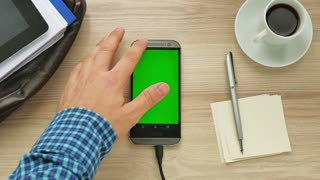 Man using a modern smartphone with green screen at her desk - green screen for placement of your own content