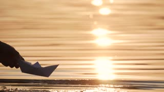 Man with a paper boat in water over beautiful sunset. Origami ship Sailing. Dreams, future, freedom or hope concept.