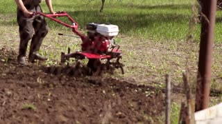 Man with motor-block in the garden. The garden tiller to work close up, walk-behind tractor