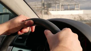 Man's hands holding steering wheel of car