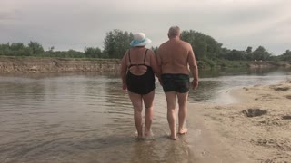 Mature Couple -- embrace overlooking river. Beautiful couple of seniors near water. Old happy people holding hands outdoors. Togetherness between aged people.