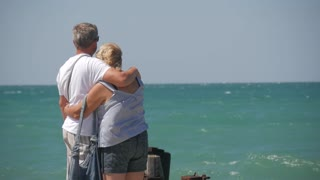 Mature Couple -- embrace overlooking sea. Beautiful couple of seniors near water. Old happy people holding hands outdoors. Togetherness between aged people.