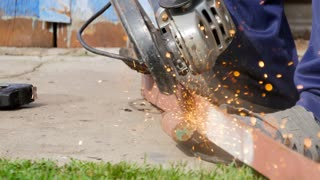 Mechanic cutting metal with handheld grinder causing many sparks. Angle Grinder Metal sawing with flashing sparks close up and Repairman hands home repair garden working summer time.