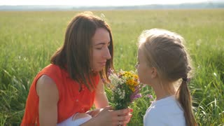 Mom and daughter in a field of flowers. Happy family mother and child daughter have fun on flowers. Cheerful daughter gifts bouquet of flowers to her mother.