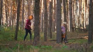 Mom and little daughter go on the road in the autumn forest. The family gather mushrooms and berries in the forest on a sunny day. Mother and daughter walking in the woods. Spending time outdoors.