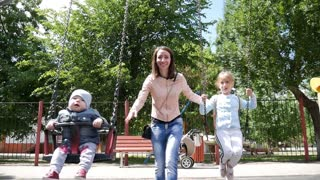 Mom children swing in the park lifestyle active.