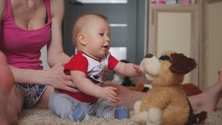 Mom with a children playing with a plush toys