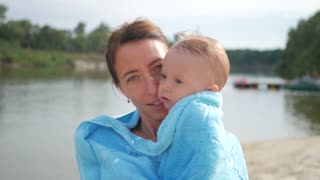 Mother and baby boy on towels on beach. Adorable little boy gets wrapped in a towel after a bathing.