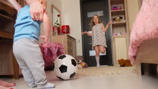 Mother and children in the room of the house playing with soccer ball