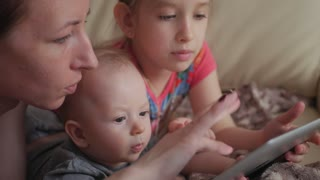 Mother and children with a tablet computer at home watching cartoons and playing.