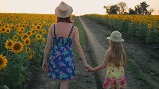 Mother and daughter at the sunflower field. Mother and daughter in hats are walking through sunflowers field. The concept of the family.