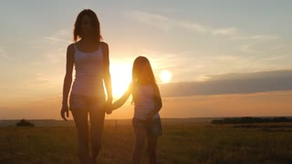 Mother and daughter walking and holding hands in the meadow at sunset.