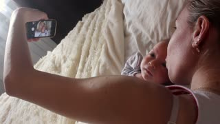 Mother and newborn baby doing selfie on bed.