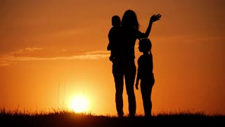 Mother and two kids silhouettes at sunset. Concept of friendly family.