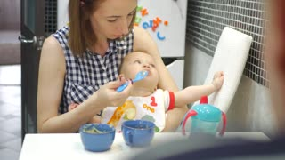 Mother feeding baby food to baby. Baby eating food on kitchen.