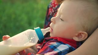 Mother feeding her baby son with a bottle of milk on the outdoor.