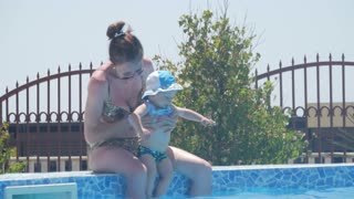 Mother holding her baby boy and he having fun in swimming pool.